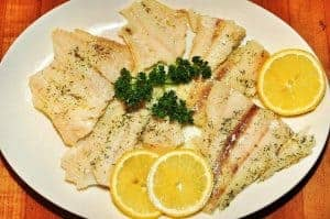 Fish with lemon slices on a plate