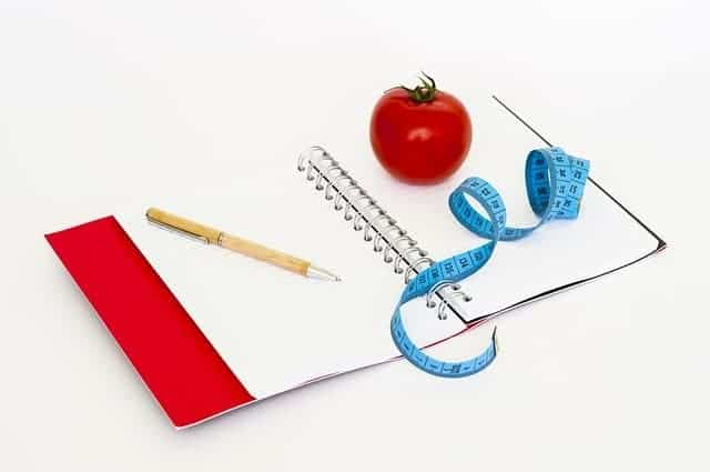 a notebook, a pen, a measuring tape and a tomato
