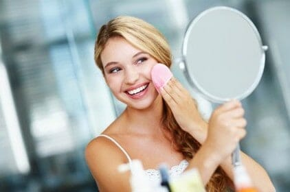 a woman washes off her make-up