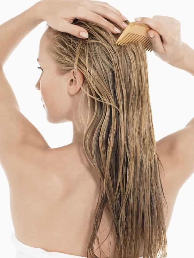 a woman combs her washed hair
