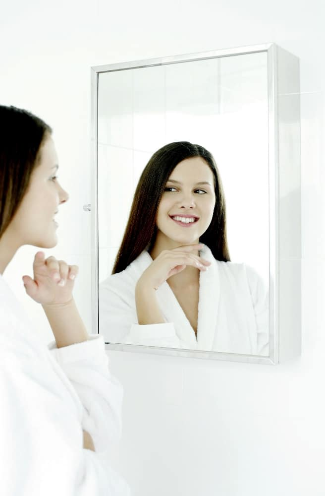 a woman looks in the mirror
