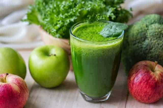 Vegetable green smoothie in a glass and apples