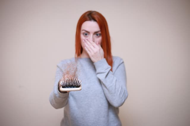 a woman looks at a hairbrush full of hair