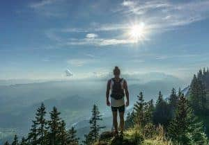 a woman in the mountains looks at the sun
