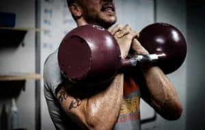 a man exercises with barbells