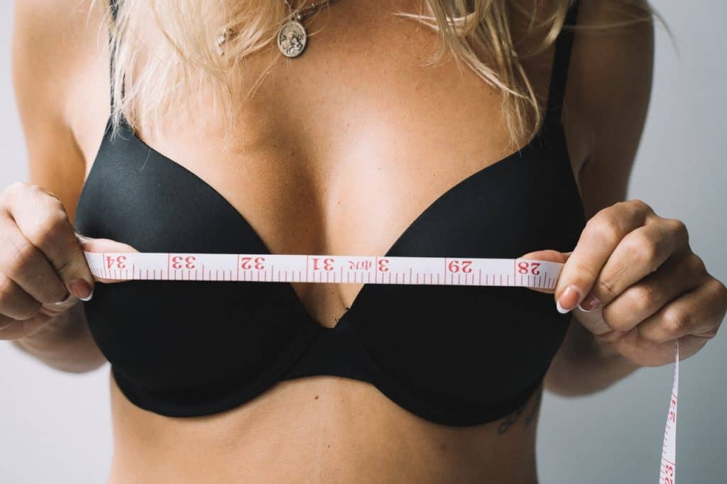 woman measures her breasts with a centimeter