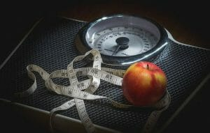 A measuring cup and an apple lying on a room scale