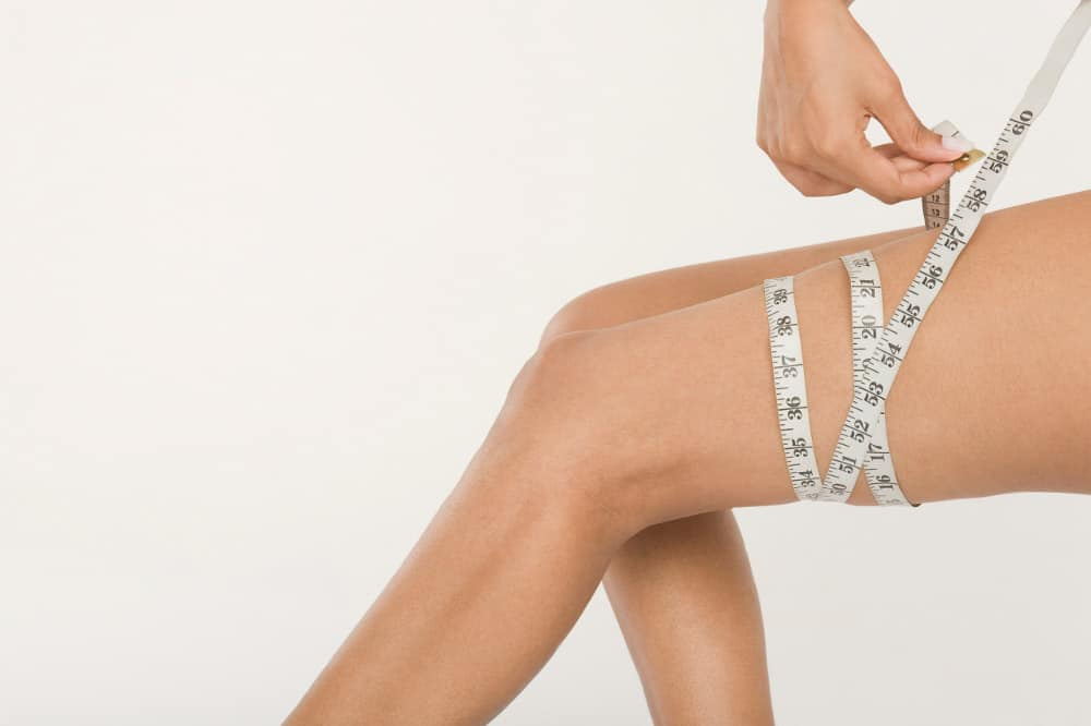woman measures thigh circumference