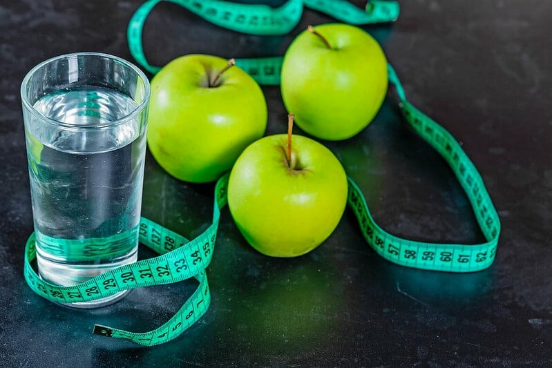 A glass of water, green apples and a measuring tape