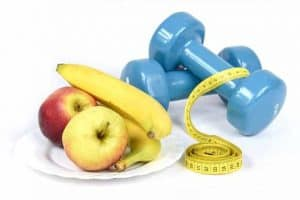 fruit, measuring tape and dumbbells for exercise