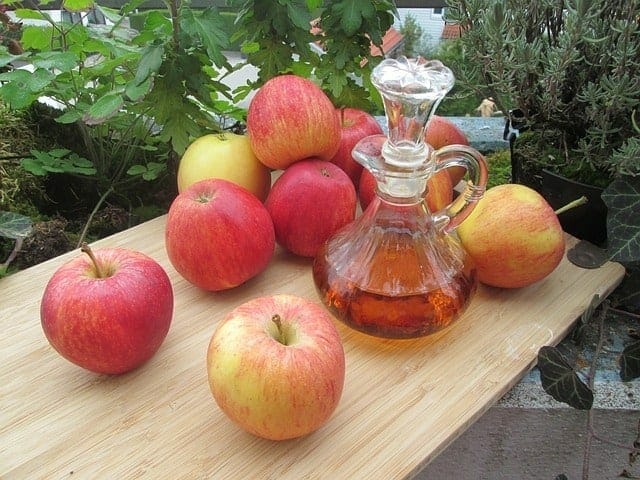 Fresh apples and a bottle of apple cider vinegar on the table