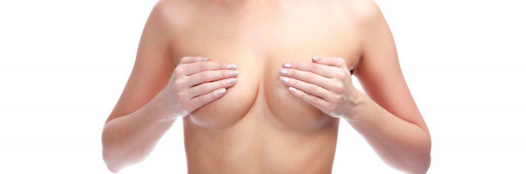 woman covers her breasts with her hands