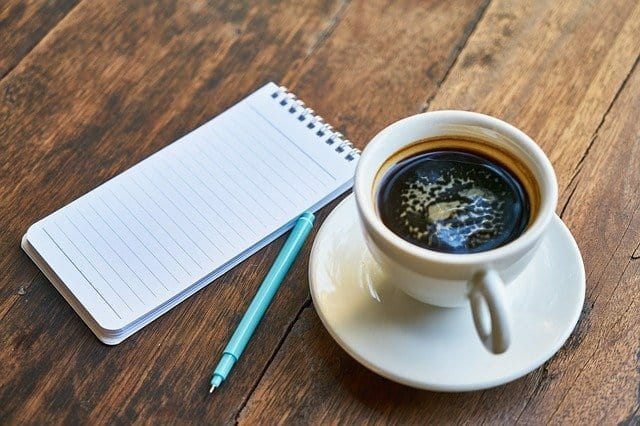 a cup of coffee, a notebook, a pen