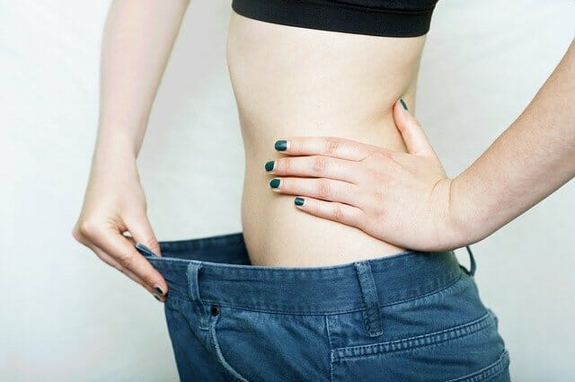 Woman in trousers several sizes too big, losing weight