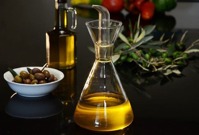 a bottle of olive oil and green olives