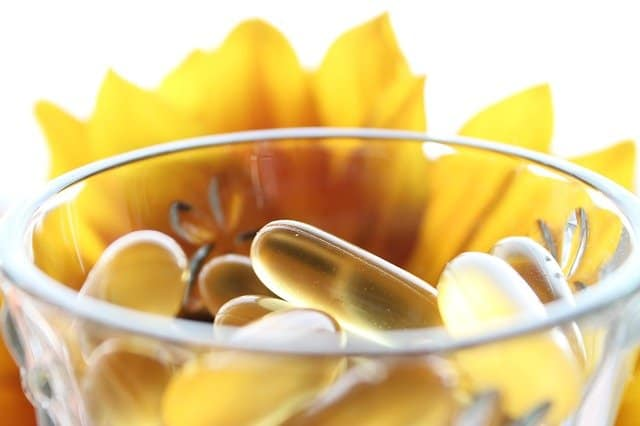 Pills in a glass, yellow flower in the background