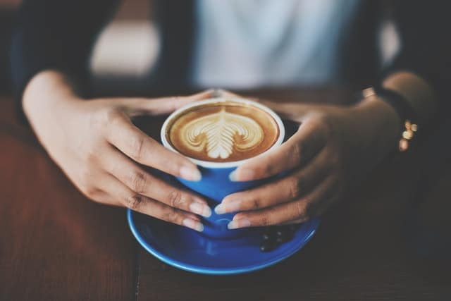 A cup of coffee held in the hands