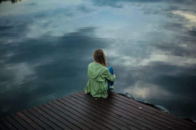 a woman sits on the edge of a pier and looks into the water