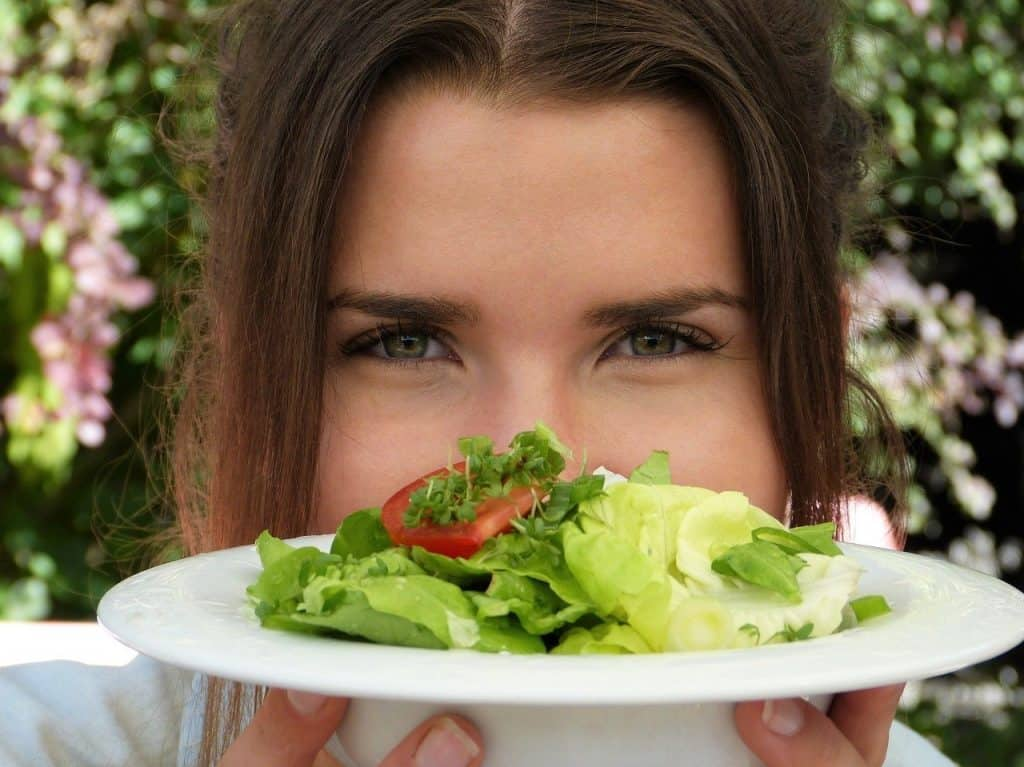 a woman holds a plate of salad