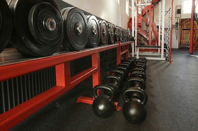 weights placed on a shelf and dumbbells on the gym floor