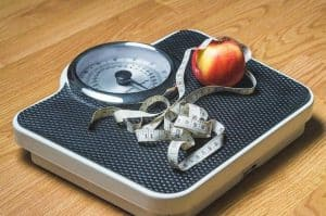 an apple and a measuring cup lying on the scale