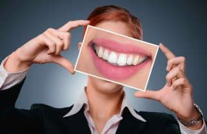 woman shows us a photo of her teeth