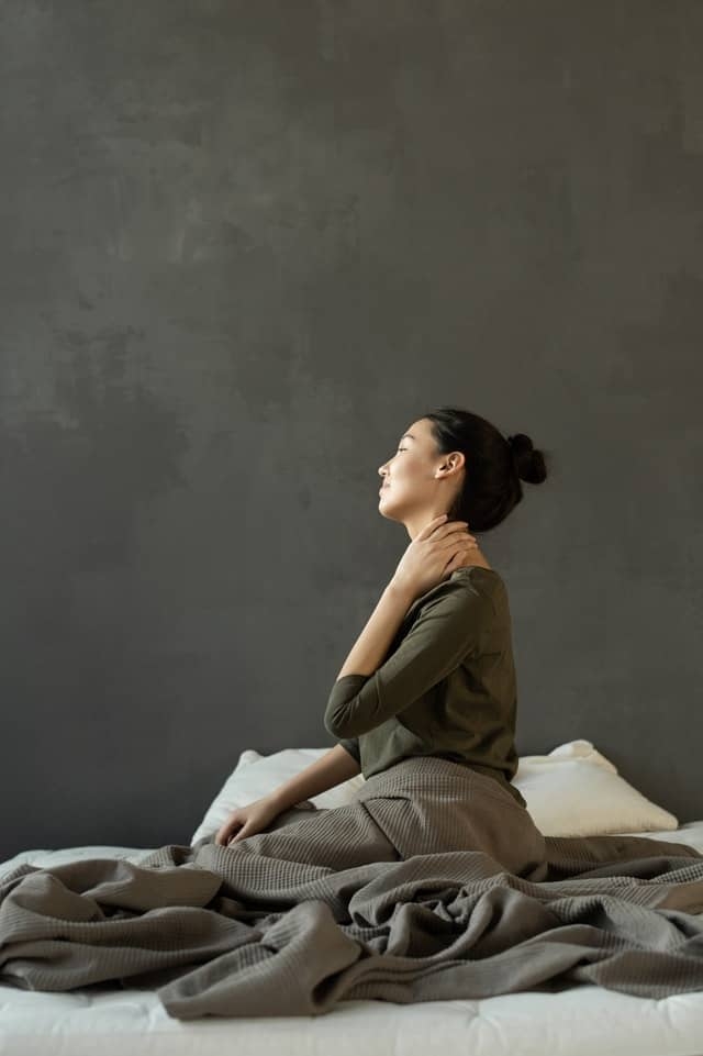 woman sitting on a bed and holding her neck, back pain