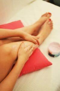 woman lubricates legs with cream