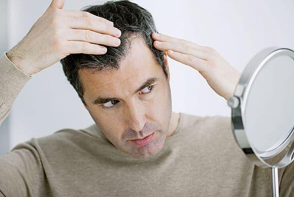a man looks at his hair