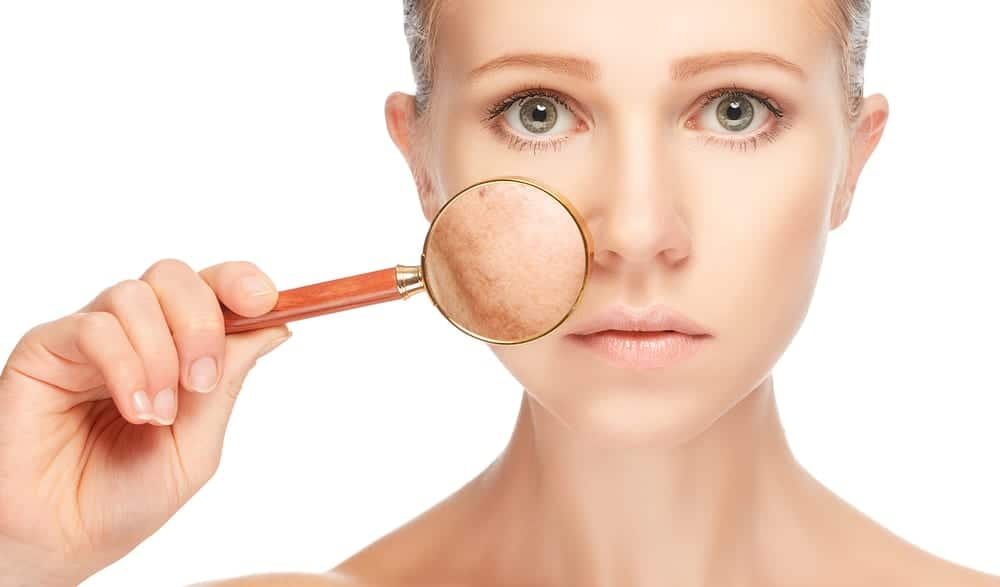 A woman looks at her complexion through a magnifying glass