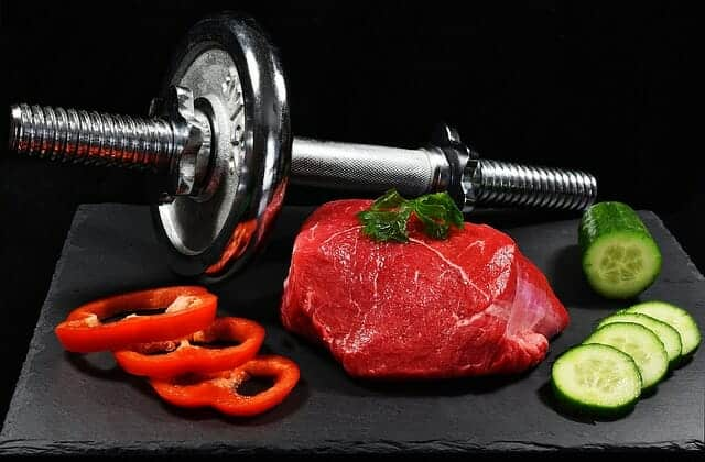 dumbbells, a piece of meat and vegetables