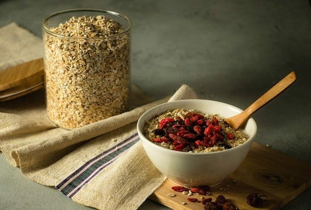 A jar with oatmeal, next to it a bowl with oatmeal