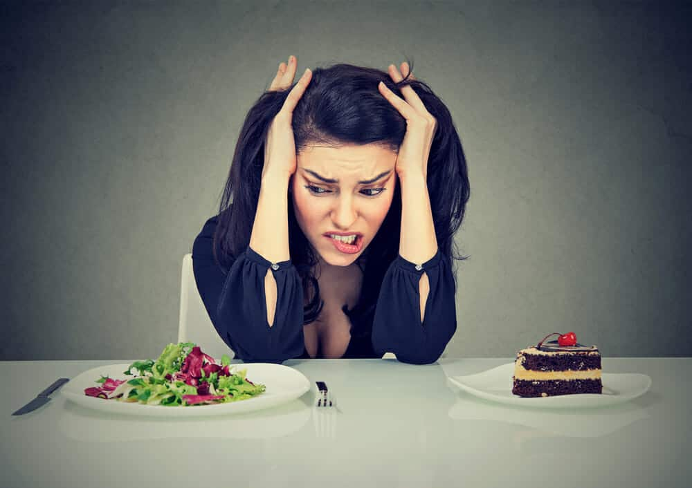 a woman sits at a table with a plate of cake and a plate of salad