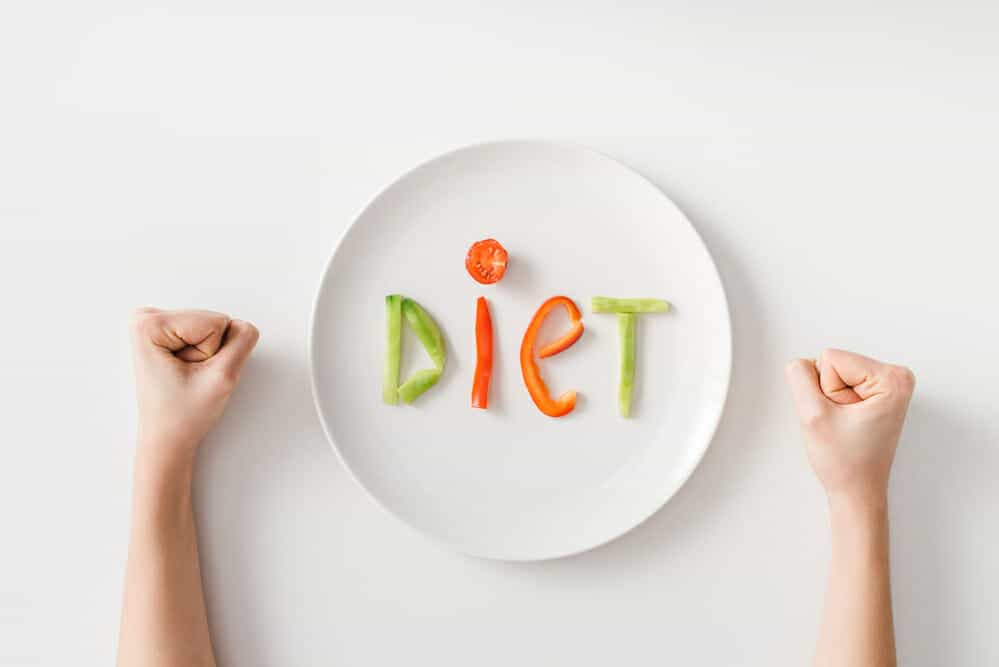 Clenched fists, a plate, a few pieces of vegetables on the plate