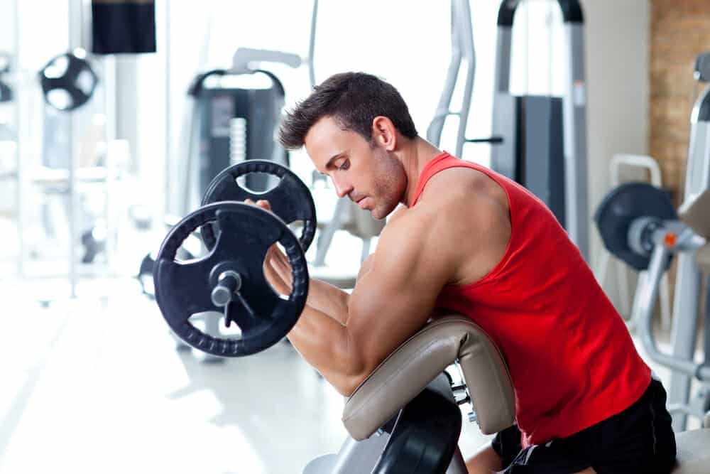 A man is exercising with a barbell at the gym.